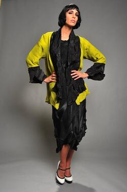 Kiwi spider-pleated jacket with black trim worn over black spider-pleated dress.